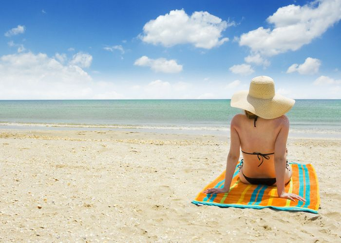 how to tan faster - tanning by the sand