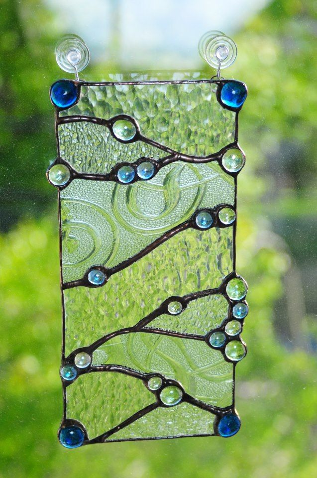 One-of-a-kind, original stained glass design. Made with reclaimed clear textured glasses and blue, green, and clear beads. www.peaceloveglass.com