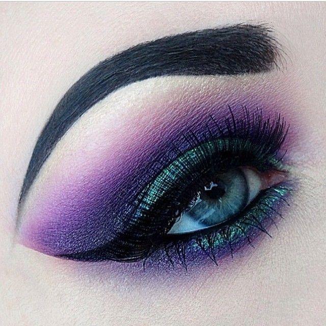 Beautiful creative makeup art in purple and green eyeshadow blue eyes eyebrows perfection love.