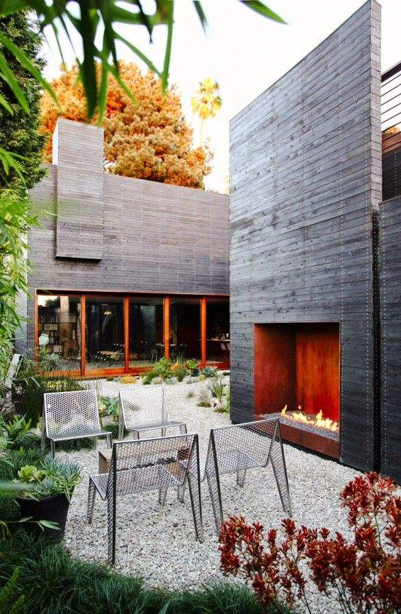 Architectural elements add height and texture in a smaller garden with clean lines, dramatic fireplace, gravel floor, airy furniture.