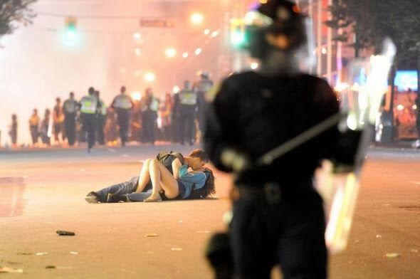 Joven australiano besa a su novia canadiense caída en el suelo luego del avance de la policía anti-disturbios en Vancouver, Canadá.