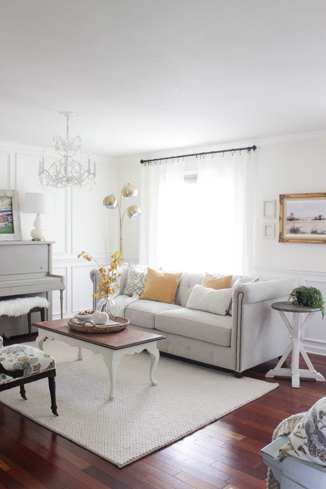 Gray painted piano, tufted couch, and yellow fall accents