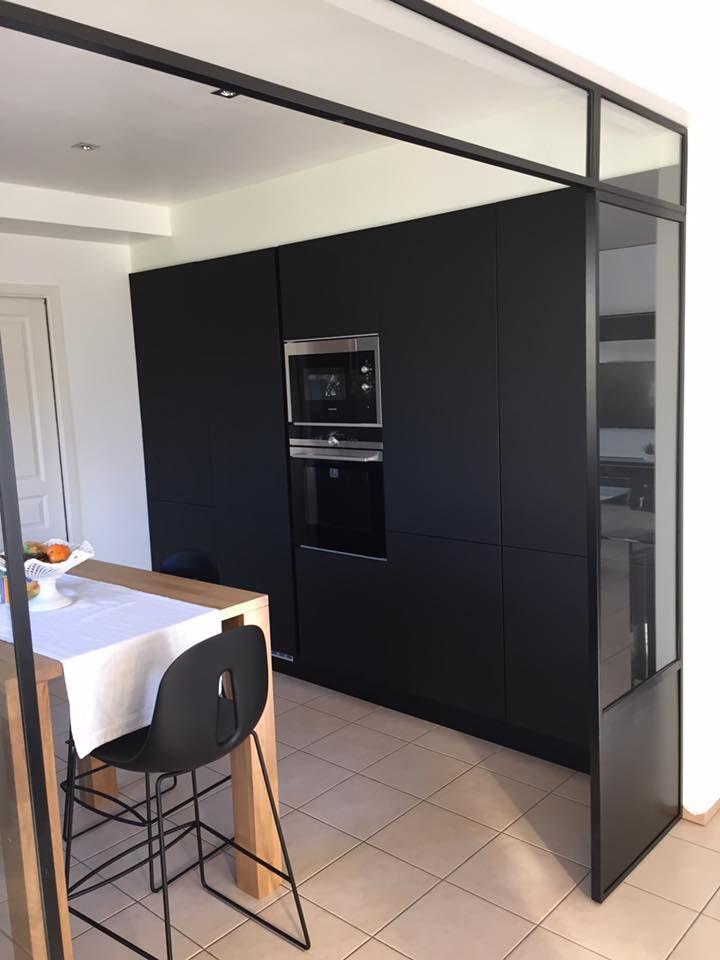 Une cuisine design semi-ouverte sur le séjour réalisée par Arthur Bonnet Quimper. La verrière en arche apporte une douche industrielle à cet espace épuré contemporain.