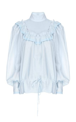 This **Flow The Label** Blue Ruffled Bib Blouse features a high ruffled neck with a ruffled bib and drawstring details.