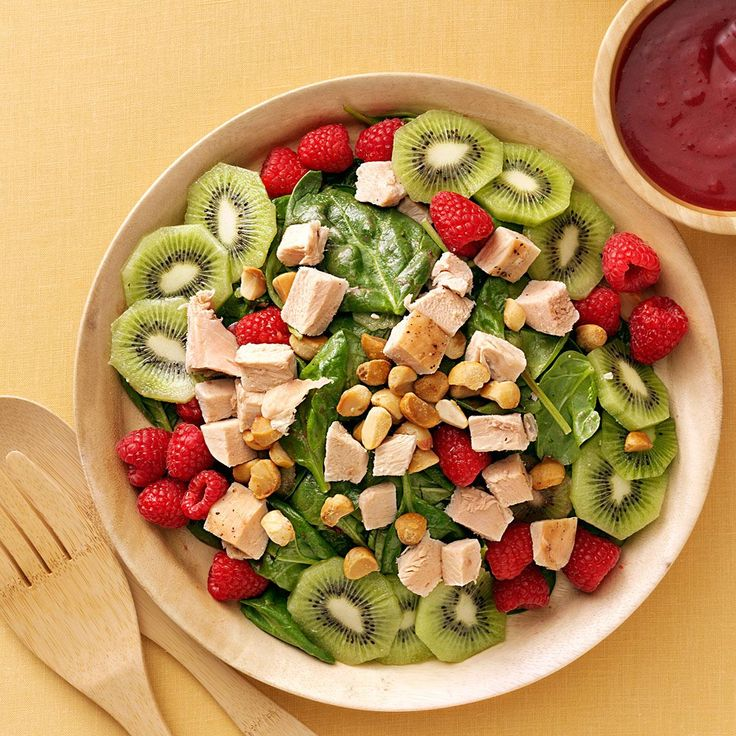 Turkey Spinach Salad with Cranberry-Raspberry Dressing Recipe -A colorful way to keep celebrating, this dish works as an entree or a side salad. If you don't want to use macadamia nuts, try fried wonton strips.—Elizabeth King, Duluth, Minnesota