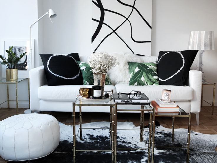 Carolina Engman's New York apartment with palm tree pillows, a white pouf, a white leather sofa, and metal bamboo tables // living rooms