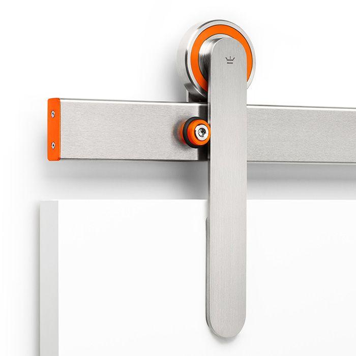 The Oden #modern sliding door hardware system shown in Face Mount in the orange color kit.