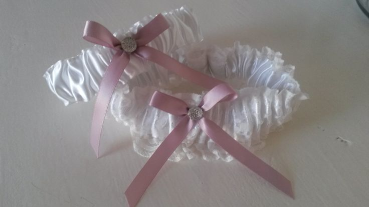 Main garter:  White satin, white lace with a soft pink centre tied bow. Tossing garter:  White satin with pink centre tied bow. louise@heavenlygarters.co.za