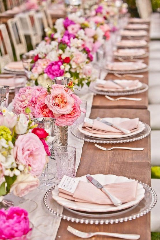 Long table setting with flower arrangements. I love the clear charger plates!