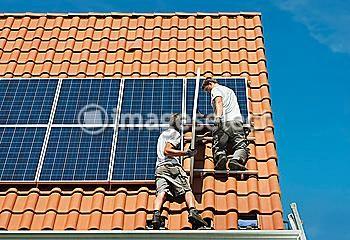 http://www.imageselect.eu/en/media/viewImage/77372718/Workers-installing-solar-panels-on-roof-framework-of-new-home-Netherlands