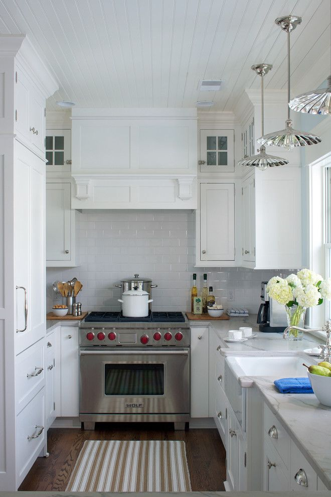 Example Of A Small Country U Shaped Enclosed Kitchen Design In Other With White Cabinets Quartzite Countertops White Backsplash Subway Tile Backsplash Stainless Steel Appliances And A Farmhouse Sink
