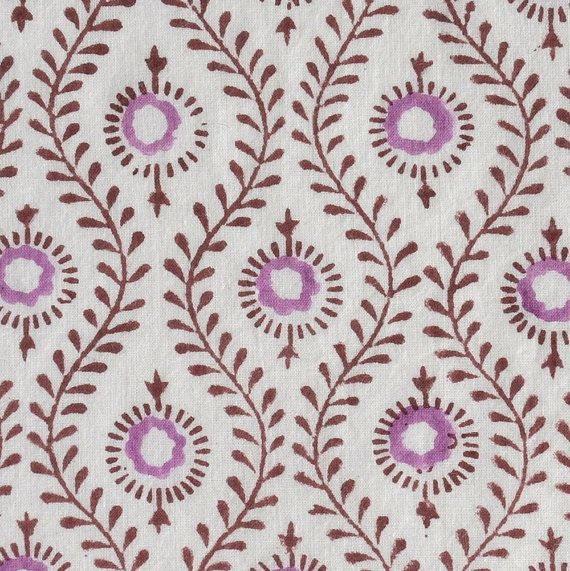 This light soft cotton cambric is hand block printed in India. It features a lovely peacock-inspired print pattern in orchid and burgundy on a white