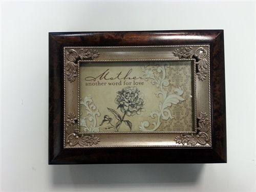 """This beautifully bordered music box makes a great gift. It comes in a beautiful dark finish with a silver detailed border. The message has a beautiful flower with an elegant background. The message says, """"Mother, another word for love."""" This box is 8""""L x 6""""W plays Wind Beneath My Wings. Use the photo opening to add your own special touch of personalization."""