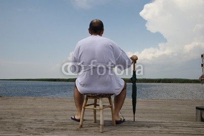 Man dressed with a white bathrobe sitting on a stool front of the Danube Delta, Romania
