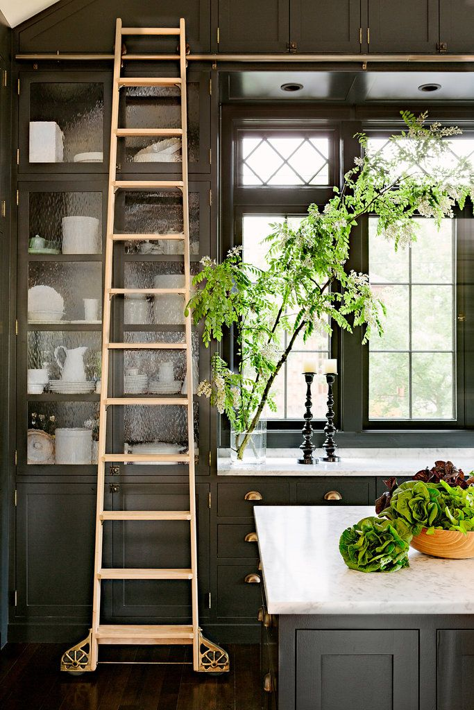 Black and white kitchen, full tall black cabinets, gold ladder via planetedeco
