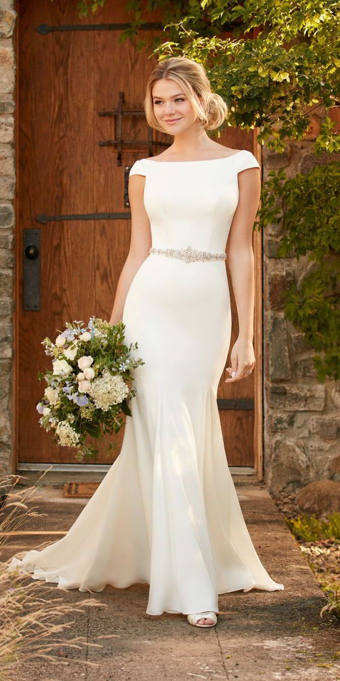 This boat neck wedding dress from Essense of Australia is the perfect combination of modest and sexy. With elegant cap sleeves, and a traditional high neckline, this crepe gown hugs – and shows off – your curves with its visible seaming before extended into a dramatic train. A detachable Diamante-beaded belt highlights the waist, and a plunging V back completes the look. The back of this gown zips up beneath fabric buttons that extend through the train.