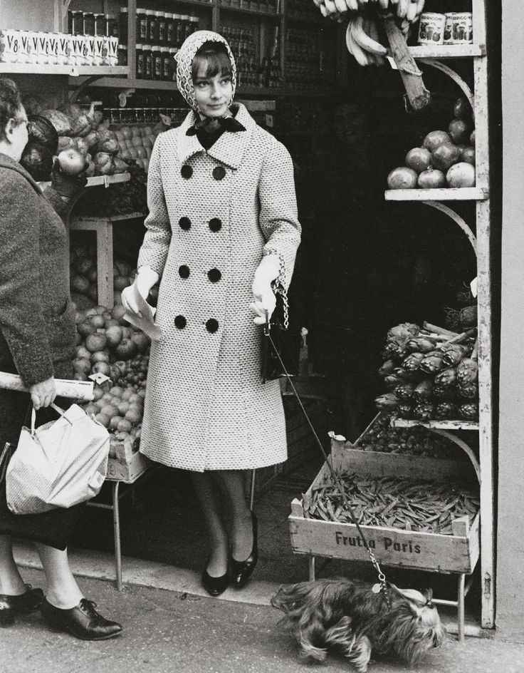 Audrey Hepburn photographed with Assam of Assam (her Yorkshire Terrier) by Elio Sorci at a grocery in Rome (Italy), in November 1961.Audrey was wearing:Coat: Givenchy (of wool, white background with a weft in the navy blue color, double-breasted with buttons of resin in the navy blue color, with collar à revers and sleeves with height above the wrists, length below the knees, liner of silk taffeta in the navy blue color, of his collection for the Autumn/Winter 1961/62).