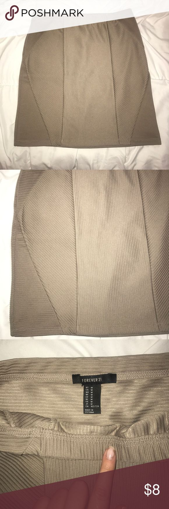 """Forever 21 tan bandage skirt Bandage-style mini skirt. Waist measures about 13"""" across and is about 16"""" in length (pictured). Bought the skirt with a small hole on the side seam and sewed it up again (pictured). Otherwise in perfect condition! Forever 21 Skirts Mini"""
