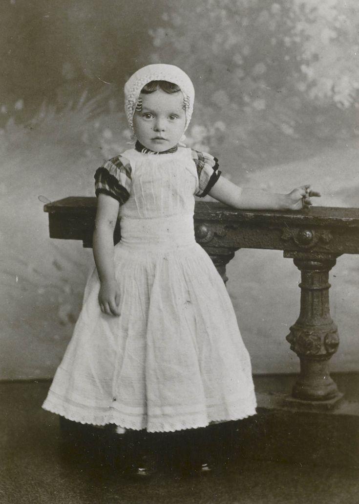 Jong meisje in streekdracht van Walcheren. Ze draagt een gehaakt mutsje, met daarin een oorijzertje met krullen aan de beide uiteinden. ca 1895 #Zeeland #Walcheren