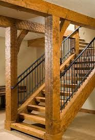 Natural wood post and beam , wood slab treads iron balusters for a clean simple rustic warm staircase Hand-hewn beams and iron. can't get any better than that