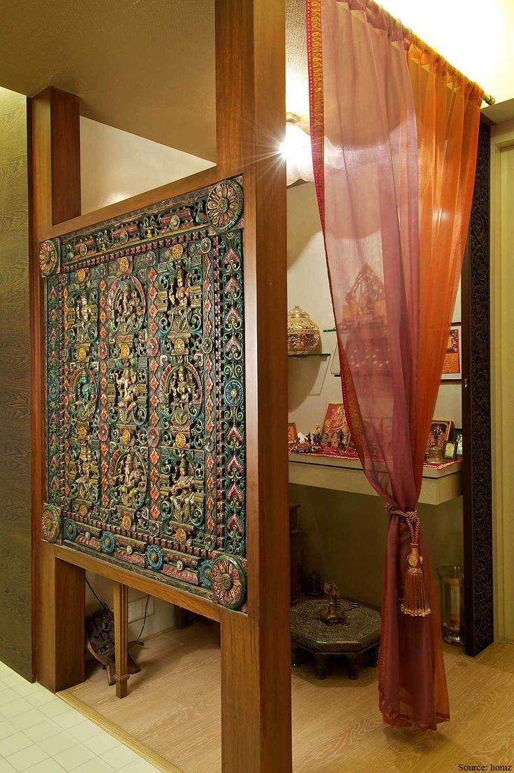 red curtain in the puja room with carving on the wooden