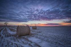 Sunset over hay bales in Saskatchewan