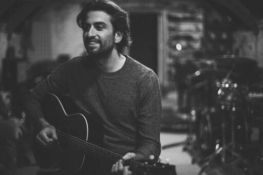 Dotan smiling with his guitar