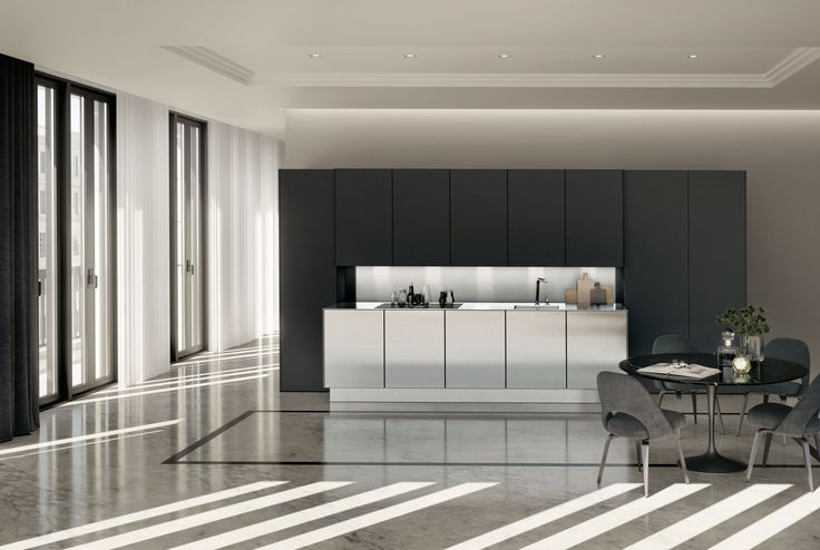 """SieMatic PURE / SE 8008 LM + SE 9009 ES: More ideas per square meter – The purist design language of this compactly planned, handle-free SieMatic with its perfectly aligned joints shows off the choice of high-quality materials in polished stainless steel combined with matt lacquer in """"graphite grey"""" to their full advantage. Thanks to new AntiPrint coating, opening the doors with the touch of a finger leaves no trace, even on matt lacquer."""