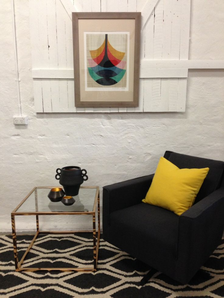 Sexy Luxe: Bold patterned woollen rug, charcoal grey swivel chair with citron cushion.  Polished copper side table and funky framed print.