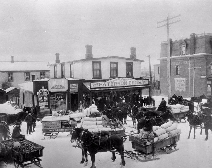 """A turn-of-the-century photo of Danforth Avenue's north side, looking west from Dawes Rd., showing some inhabitants of """"Little York"""" buying their winter feed from Paterson Brothers' shop."""