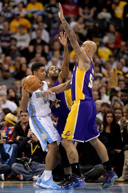 Description of . DENVER, CO - DECEMBER 30: Wayne Ellington (2) of the Los Angeles Lakers and Robert Sacre (50) defend Gary Harris (14) of the Denver Nuggets during the second half of the Lakers' 111-103 win. The Denver Nuggets hosted the Los Angeles Lakers at the Pepsi Center on Monday, December 30, 2014. (Photo by AAron Ontiveroz/The Denver Post)