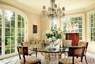 In the dining room of his Washington, D.C., home, designer Thomas Pheasant paired a French chandelier with a table of his own design. The painting is by Robin Rose, and the sculpture is by Eva Hild | archdigest.com
