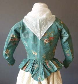 Green Brocade Caracao, 1780's, turquoise taffeta silk woven with sprays of soft vermillion red, yellow, apricot, green and ivory and others of soft apricot and silver, with a silvery background lace effect weave, the front with turned back pointed revers and long pointed front, the sleeves with wrist slits, the back with pointed tail and a softly pleated skirt, lined with linen back neck to hem 17 in or 43 cm. Meg Andrews - Antique Costumes and Textiles