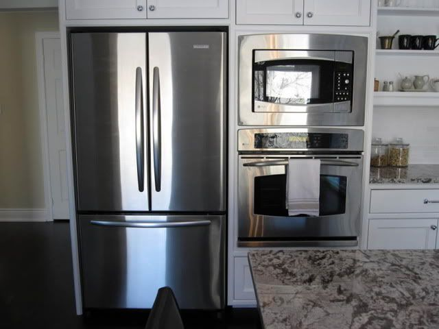 Double wall oven beside refrigerator with white cabinets for Double kitchen cabinets