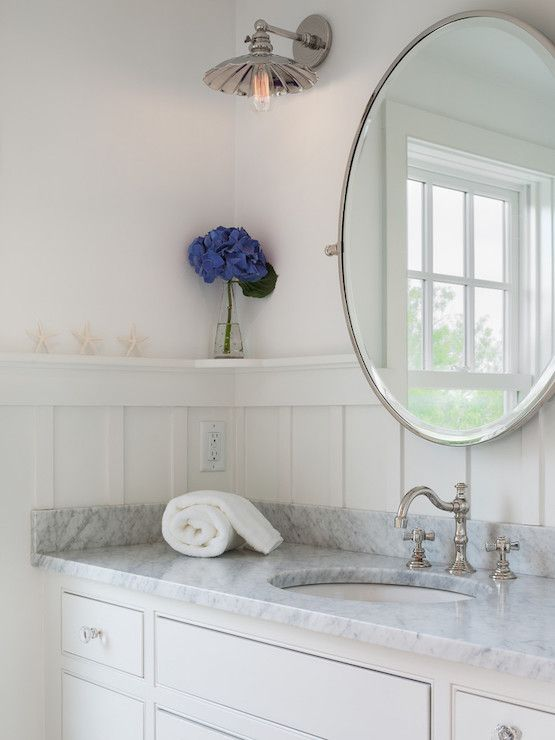 Note the shelf above the board and batten.  Bathroom with Board and Batten, Cottage, Bathroom, Sophie Metz DesignBeautiful cottage bathroom features upper walls painted creamy white and lower walls clad in board and batten with shelf alongside an oval pivot mirror flanked by metal vintage barn wall sconces over a white bathroom vanity topped with gray marble framing oval sink and vintage hook and spout faucet.