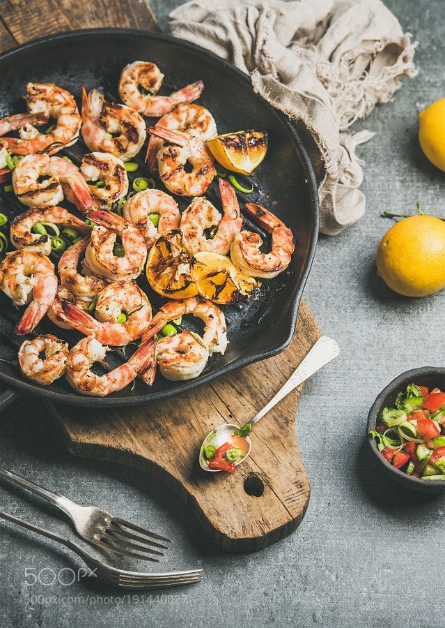 Seafood dinner with grilled tiger prawns in pan grey background by 2enroute