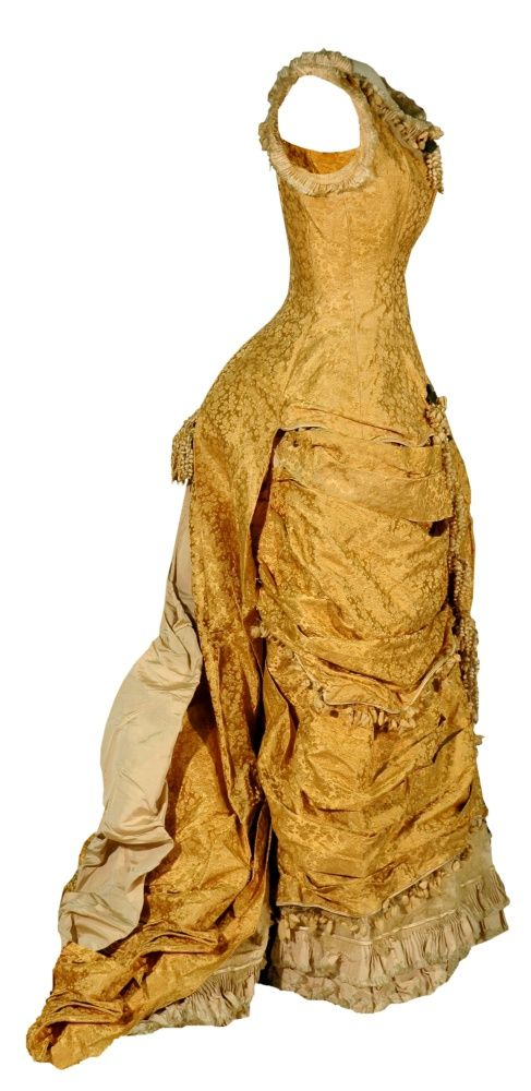 Gold brocade gown, 1878.The fabric would nicely reflect the light cast by gas chandeliers in a ballroom. Its bustle effect is achieved by a silk rep underskirt lined in stiff, coarse fabric. The long train has a series of beige silk flounces and ruffles at the end. Edges are trimmed with a delicate fringe of cloth bellflowers and rosebuds strung on wire.
