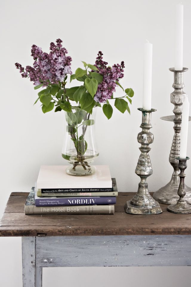 CONSOLE STYLING :: Stack of coffee table books in coordinating colors w/ a vase and gorgeous candlesticks in varying heights. | #tinek