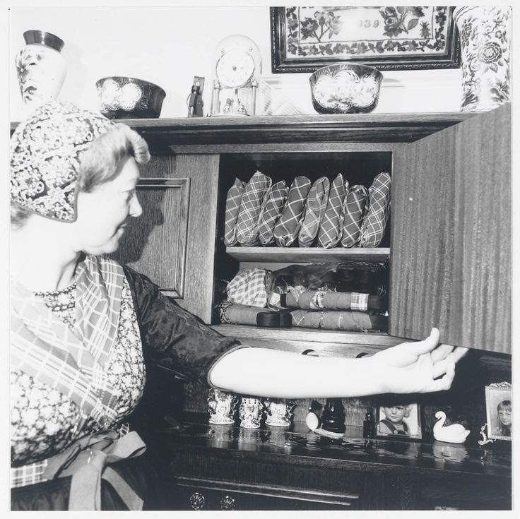 Demonstratie van het vouwen van kleding in Staphorst-Rouveen door Mevrouw J. Timmerman-Slager uit Rouveen, t.b.v. onderzoek voor de tentoonstelling 'Kleding met een vouwtje' in het Nederlands Openluchtmuseum. Mevrouw Timmerman laat zien hoe haar tot kleine pakketjes opgevouwen schorten in de kast worden bewaard.