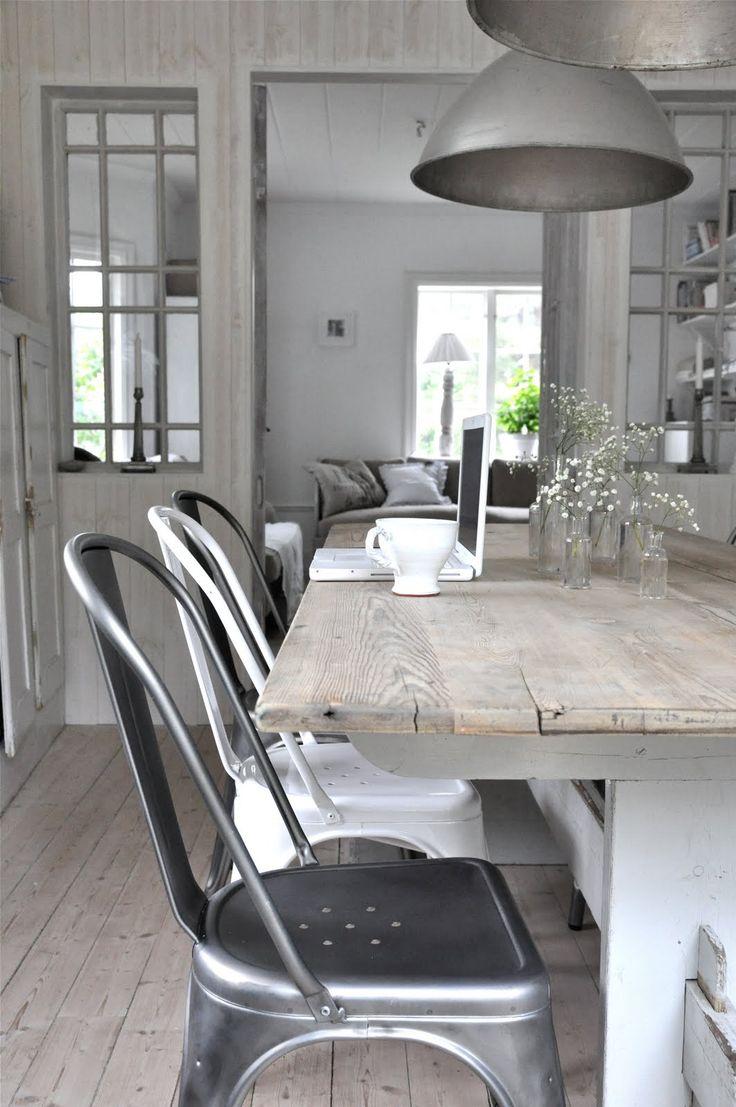 Witte tafel met houten blad en tolixstoelen.