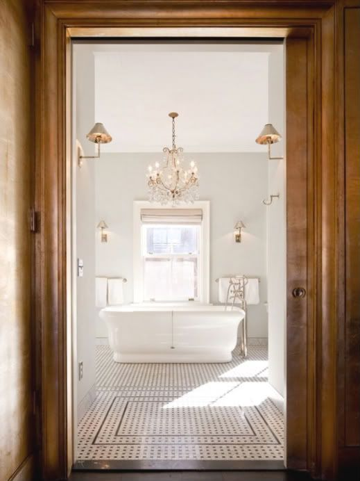 Beautiful airy bathroom, gold sconces, graphic tile floor, large pedestal tub