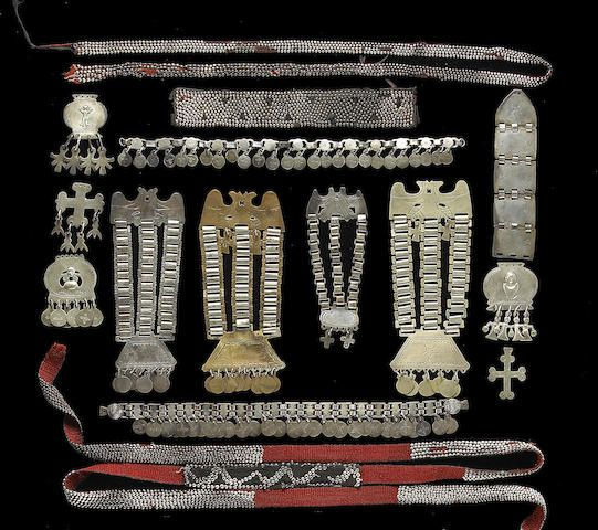 A collection of Mapuche silver jewelry Including five breast ornaments, sequil, four with incised avian decorations at top; three pendants with human effigy designs; two cross pendants, trapelacucha; two head ornaments with suspended ornamental discs, trarilonco; and three cloth or woven belt panels studded with silver half-beads, ngutroe.