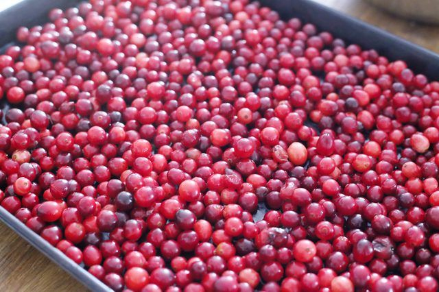 How to Dry Fresh Cranberries-Drain the water and sprinkle the berries with sugar or drizzle with corn syrup. If you do not want sweetened cranberries, omit this step. Spread the cranberries in a single layer on a cookie sheet, and put them in the freezer for two hours. Washington State University says that the freezing process helps the berries dry faster.