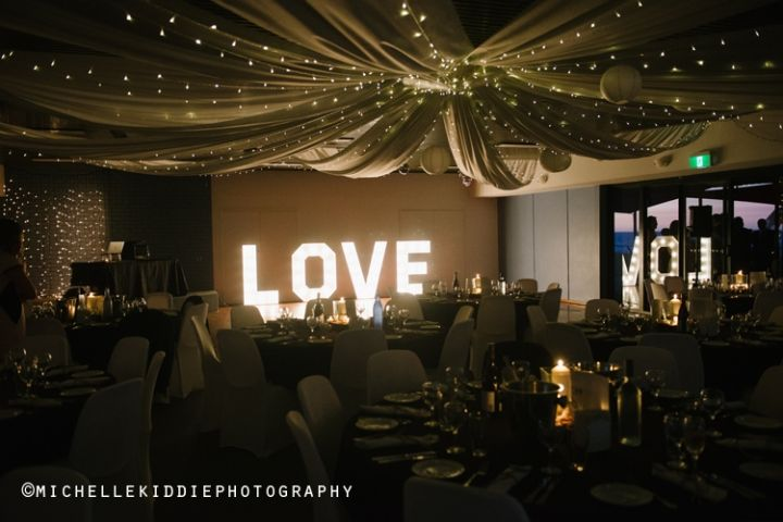 The Floreat Beach Surf Lifesaving club was completely transformed for this couple's beach wedding. They hired the big love sign and draped silk material from the ceiling with fairy lights to transform a basic function room into a stunning and stylish setting.