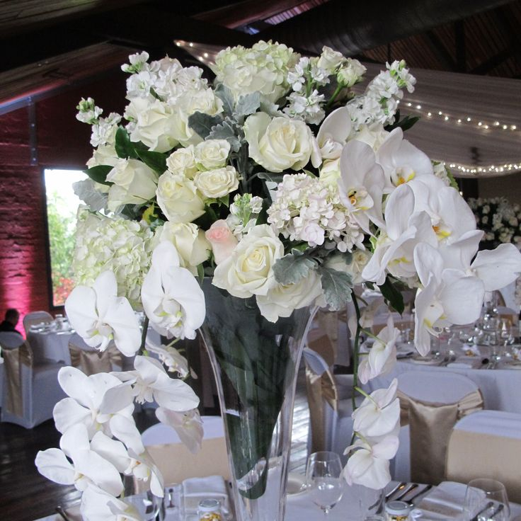tall arrangement of roses, stocks, hydrangeas and Phalaneposis Orchids