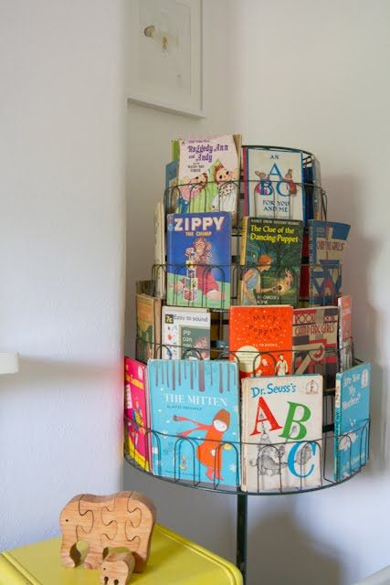 Cute book idea for the home - a revolving shoe rack becomes a revolving book holder easy for kids to look at each book before choosing what they want. AND easy for the kids to put the books back
