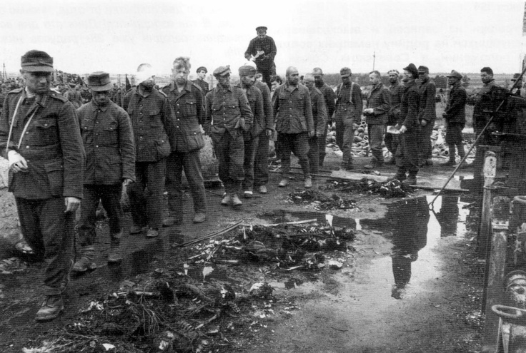German POWs are made to parade past the crematorium ovens at the Majdanek concentration camp. Next to the POWs on the ground lie remains of those victims burned in the ovens barely seen on the right of the picture. Lublin, Poland, 1944.