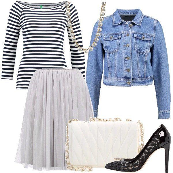Una gonna in tulle bianco, come vogliono le ultime tendenze, una maglia navy con spalle leggermente scoperte, una giacca in jeans, delle décolleté in pizzo e vernice ed infine una tracolla Versace bianca e una luminosa collana con grossi strass ci riportano, rivisitandoli, nei magnifici anni '80.