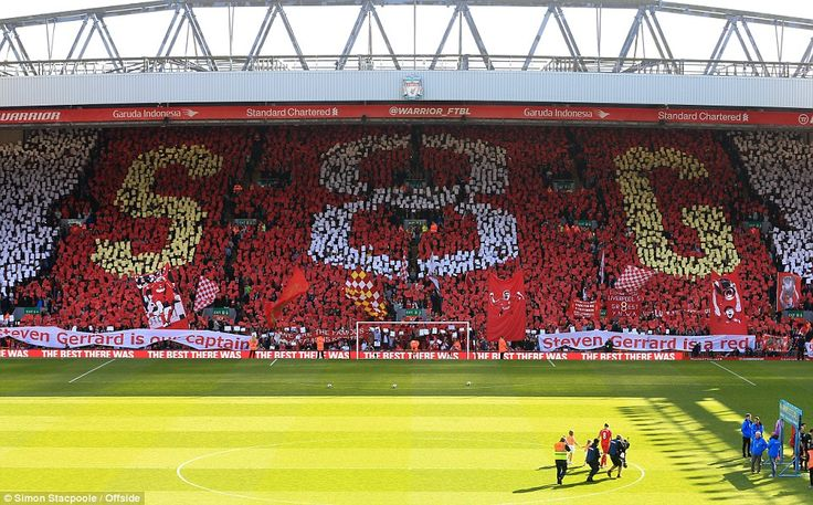 Kopite through and through: Gerrard looks up at the the famous stand's tribute to him, wit...