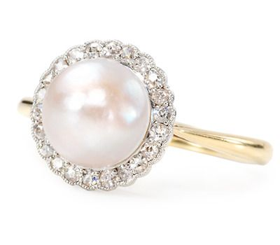 South Sea cultured pearl of 9.1 mm. The luscious white pearl with wondrous overtones of green, purple and cream makes this ring quite versatile with wardrobe colors. A surround of twenty-two (22) white single cut diamonds with a total estimated diamond weight of .22 carats functions as a shimmering halo for the precious pearl. All set in platinum-topped 18k yellow gold. circa 1930.